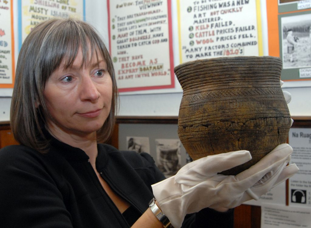 Beaker - object from Strathnaver Museum with volunteer holding