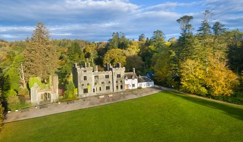 view of armadale castle with trees behind and grass in front