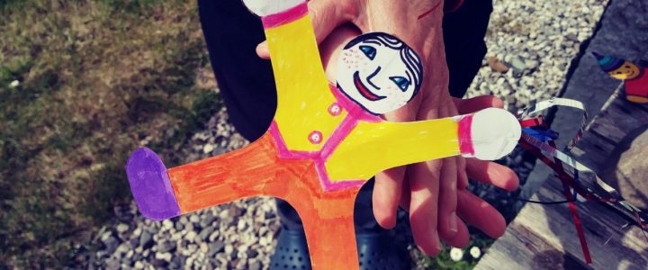 cut our puppet of a girl doing a cartwheel. coloured in orange, yellow and purple