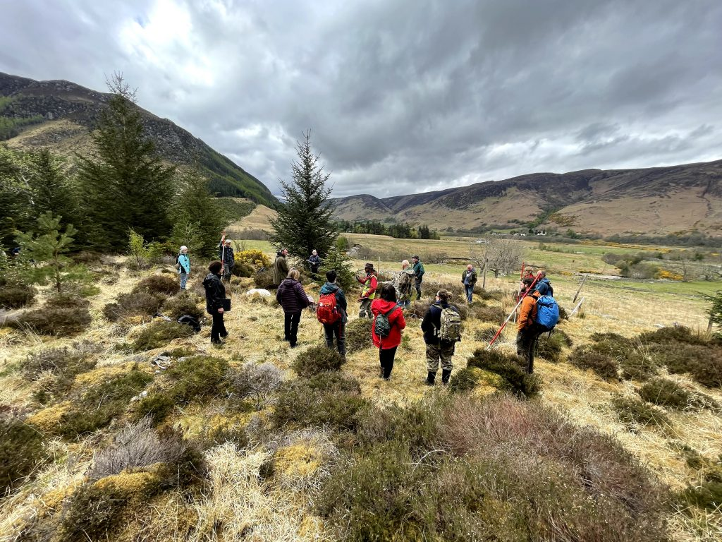 view of glen with community members standing in circle surveying site