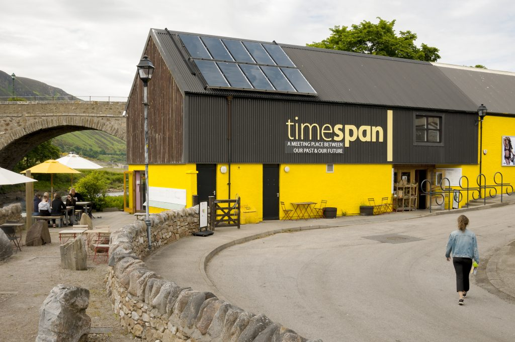 Picture of outside of Timespan museum - brown top half and yellow bottom half of building with the letters in yellow of the name (timespan) across the brown wood on the top half